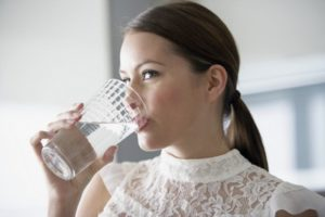 A woman drinking a glass of fresh well water.